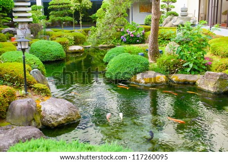 Spring flowers in the Asian garden with a pond - stock photo