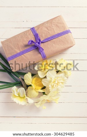 Spring flowers narcissus and  gift box  on white painted wooden planks. Selective focus. Place for text. Toned image. - stock photo