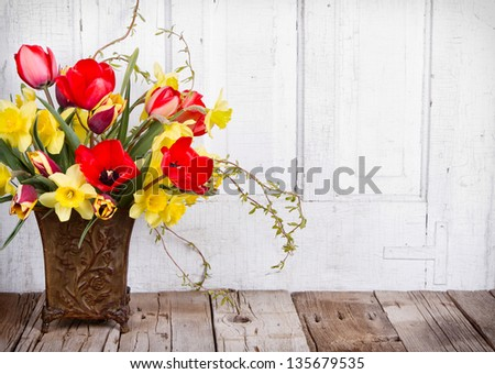 Spring flowers tulips and daffodils in a vase on a white wooden background - stock photo