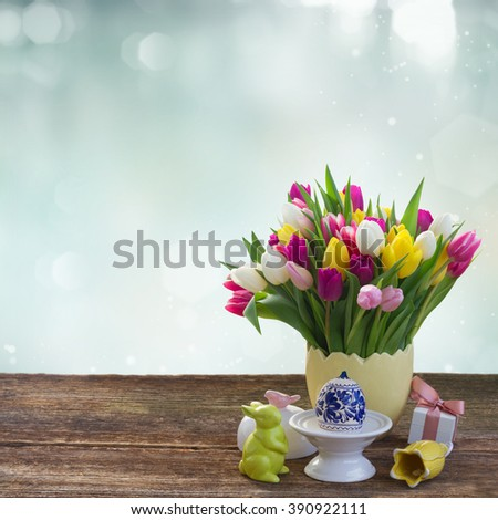 Spring fresh tulips with easter egg and bunny on table over blue  background - stock photo