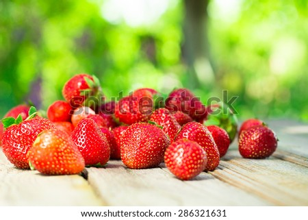 Spring fruits, strawberries on old wooden background.