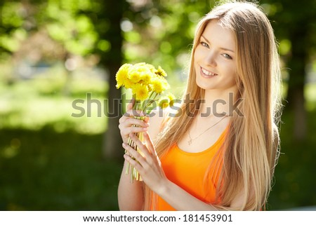 Spring girl. Lovely blond girl with bunch of dandelions outdoors. - stock photo