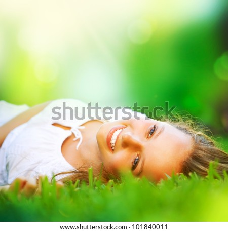 Spring Girl lying on the Field. Happiness - stock photo