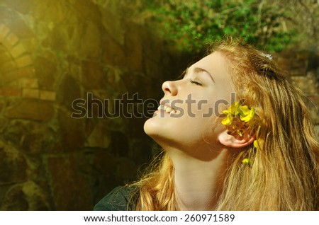 Spring girl seating on the field of dandelions. Enjoy Nature. - stock photo