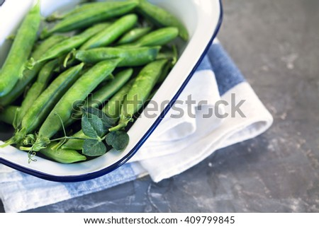 Spring green peas in white enamel dish â?? close up top view with copy space - stock photo