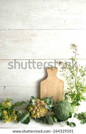 Spring green vegetables with cutting board on white wooden background - stock photo
