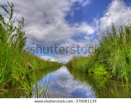 Spring HDR scene of Freshwater ditch in dutch polder landscape seen from the water level on a beautiful day with fluffy clouds and blue sky - stock photo