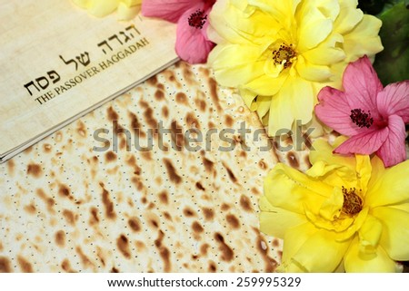 spring holiday of Passover and its attributes, with matzo and Haggadah in Hebrew - Happy Passover - stock photo