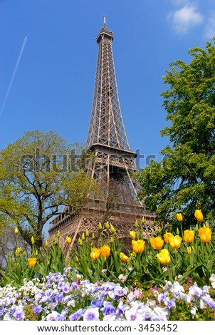 Spring in Paris, france, the eiffel tower against a vibrant blue spring sky with tulips in foreground. HDR, high dynamic range image.