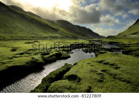 Spring in Scotland Valley: Infectious greens, winding streams, and volatile skies -- all typical of spring in Scotland.  Taken on Isle of Skye, in the Scottish Highlands. - stock photo