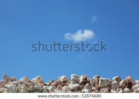 Spring in the desert. Sun-bleached stones and some dried grass - stock photo