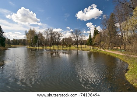 Spring in the park with white clouds and awakening nature - stock photo