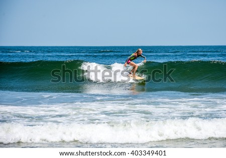 SPRING LAKE, NEW JERSEY-AUGUST 1 - A girl rides the wave along the coast on August 1 2015 in Spring Lake New Jersey. - stock photo