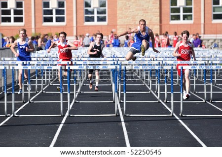 SPRING LAKE PARK, MN - APRIL 20: Runners from Spring Lake Park, St. Louis Park, and Benilde-St. Margaret's complete in a high school boys hurdles race on April 20, 2010 in Spring Lake Park, Minnesota.