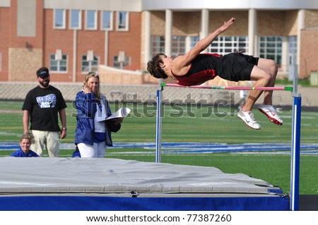 SPRING LAKE PARK, MN - May 7: Unidentified Teen Boy Doing the High Jump at a High School Track and Field Meet on May 7, 2010 in Spring Lake Park, Minnesota. - stock photo