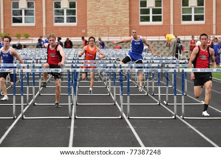 SPRING LAKE PARK, MN - May 7: Unidentified Teen Boys Competing in High School Hurdles Race on May 7, 2010 in Spring Lake Park, Minnesota. - stock photo