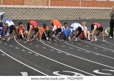 SPRING LAKE PARK, MN - May 7: Unidentified Teen Boys in the Starting Blocks at a High School Sprint Race on May 7, 2010 in Spring Lake Park, Minnesota. - stock photo