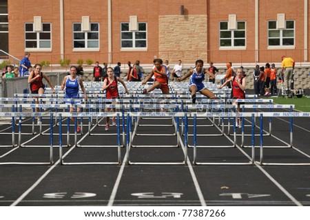 SPRING LAKE PARK, MN - May 7: Unidentified Teen Girls Competing in High School Hurdles Race on May 7, 2010 in Spring Lake Park, Minnesota. - stock photo