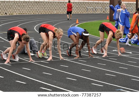 SPRING LAKE PARK, MN - May 7: Unidentified Teen Girls in the Starting Blocks at a High School Sprint Race on May 7, 2010 in Spring Lake Park, Minnesota. - stock photo
