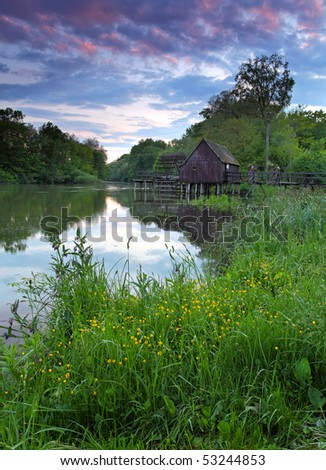 Spring landscape at sunset with watermill and river - stock photo