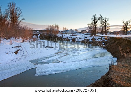 spring landscape melting of ice and snow in early spring on the river at sunset - stock photo