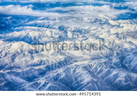 Spring landscape. Mountains with altitude in blue distance. Photo from plane