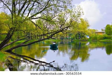Spring landscape of lake and bright trees. Rest in boat