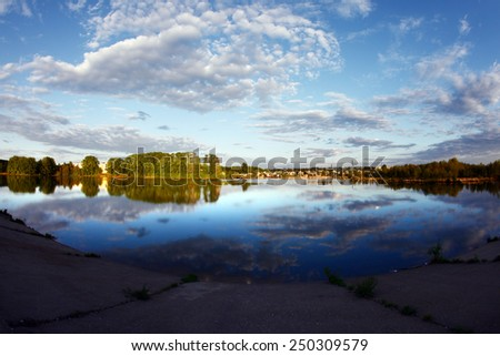 spring landscape sunset over the river near the forest and clouds reflected in the mirror water  - stock photo
