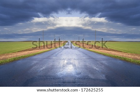 spring landscape wet road leading to the horizon amid green fields and cloudy sky - stock photo