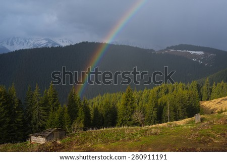 Spring landscape with a rainbow in the mountains. Beauty in nature - stock photo