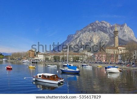 Spring landscape with boats on the Lake Como, and old church on the background in Lecco, Lombardy, Italy