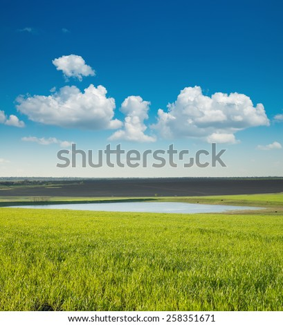 spring landscape with green field and pond - stock photo