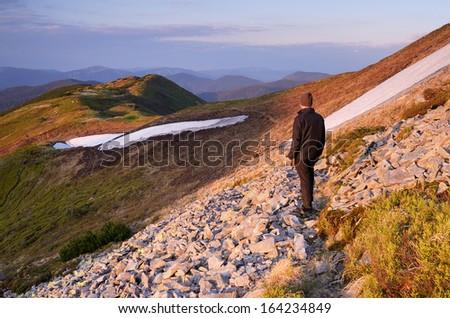 Spring landscape with man tourist on a mountain trail. Carpathians, Ukraine, Europe. - stock photo