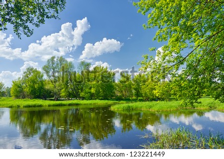 Spring landscape with Narew river and clouds on the blue sky - stock photo