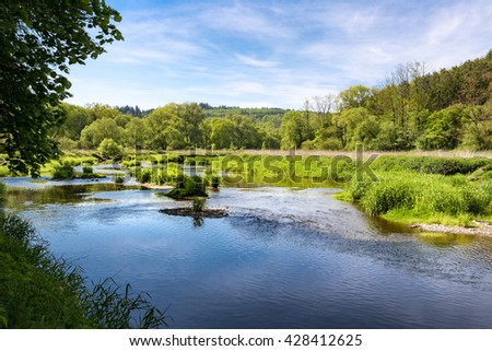 Spring landscape with river, trees and blue sky with white clouds. Oslava river, Czech Republic, Europe. - stock photo