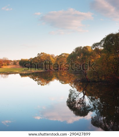 Spring landscape with river. Trees on banks of river reflected in water. Sunny evening. Reflection of cloudy sky in water - stock photo
