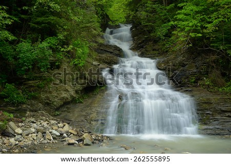 Spring landscape with the river. Beautiful waterfall in the mountains - stock photo