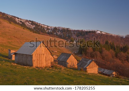 Spring landscape with wooden village of shepherds in the mountains. Light of the setting sun. Carpathian mountains, Ukraine, Europe - stock photo