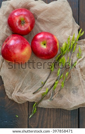 Spring letter and red apples on wooden background