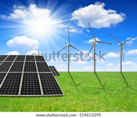 spring meadow with solar energy panels and wind turbines