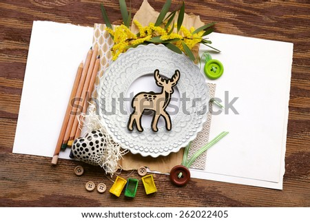 Spring nature composition with baby deer placed over shredded paper next to pencils and artistic white photo frame with buttons over white placeholder paper on the left and right and vintage wood - stock photo
