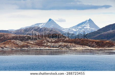 Spring Norwegian landscape with sea coast and mountains with snow - stock photo