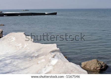 Spring on lake ontario shore with ice and snow melting fast. - stock photo