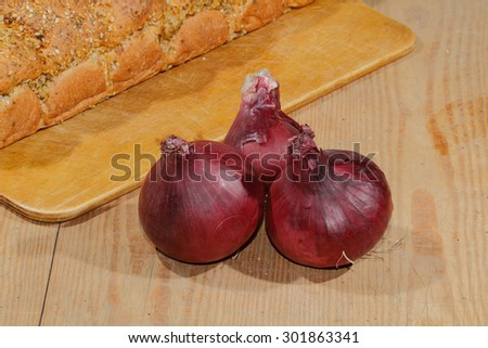 Spring onions, onions, vegetables on a wooden chopping board - stock photo