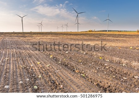 Spring or autumnal landscape with windmills on fields. Polish countryside with windmills