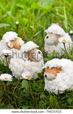 Spring- or easter decoration - funny little sheep in grass with daisies - vertical - stock photo