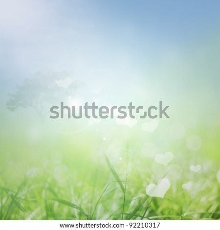 Spring or summer abstract Valentine nature background with grass in the meadow and blue sky in the back