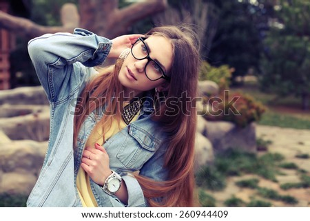 Spring outdoor fashion portrait of elegant woman posing at the street, wearing vintage denim jacket retro hipster sunglasses and jewelry.
