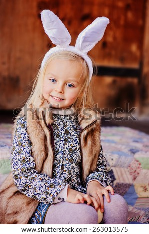 spring outdoor portrait of happy child girl wearing bunny ears for easter - stock photo