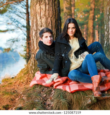 Spring outdoor portrait of young pair. Boy and girl in the spring forest sitting on vintage cover - stock photo